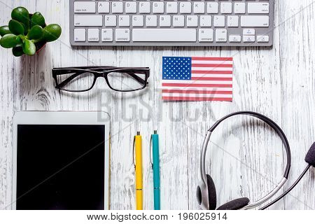 Self-education. Learning english online. Headphones and tablet PC on wooden table background top view.