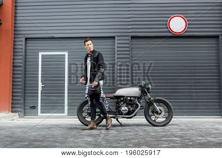 Handsome rider biker boy hold his black helmet near industrial gates and classic style cafe racer motorcycle. Bike custom made in vintage garage. Brutal fun urban lifestyle. Outdoor portrait. poster