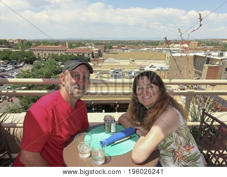SANTA FE, NEW MEXICO, JULY 4. The La Fonda Hotel on July 4, 2017, in Santa Fe, New Mexico. A Couple at a Rooftop Bar Have Seats Overlooking Santa Fe, New Mexico.