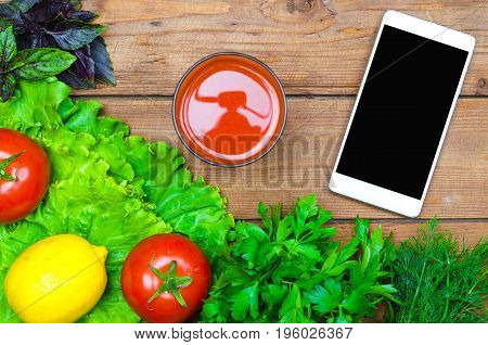 Fresh Dietary Vegetables, A Glass Of Tomato Juice And A Smartphone On A Wooden Table, Top View.