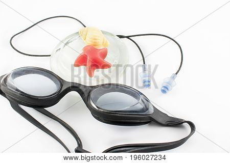 Water goggles swimming cap earplugs and star shaped jellyfish and sea snail on a white background.