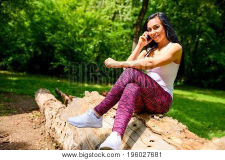 A beautiful young sporty girl sitting on a log and talking on a phone