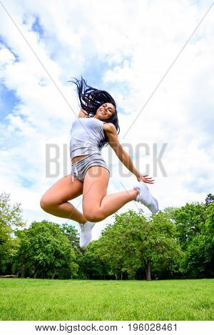 A beautiful young sporty girl jumping on a field in a park while wearing shorts and a top
