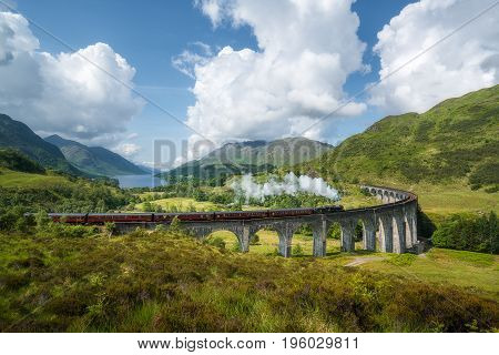 Vintage steam train passes the famous Glenfinnan viaduct with views over Loch Shiel poster