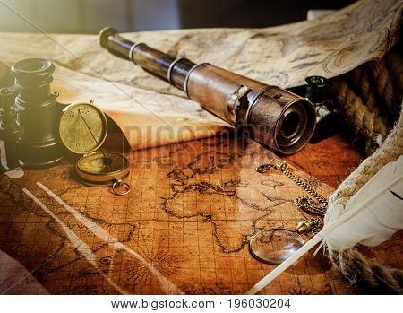 Old vintage retro compass and spyglass on ancient world map. Vintage still life. Travel geography navigation concept background. poster