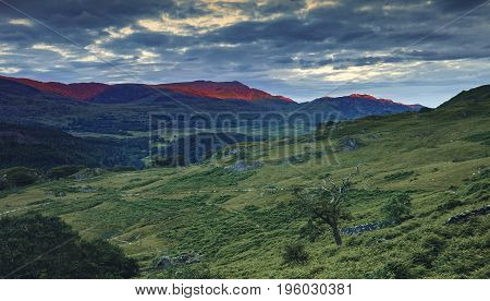 Mountain Peaks in Red Sunset Light View from Watkin Path in Nant Gwynant Valley in Snowdonia