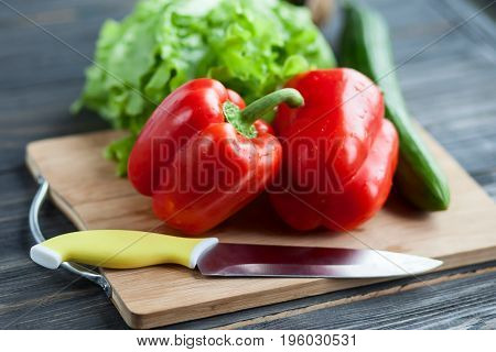Vegetables lie on a chopping wooden board on a roustic table - salad cucumber and red sweet pepper. Close up photo