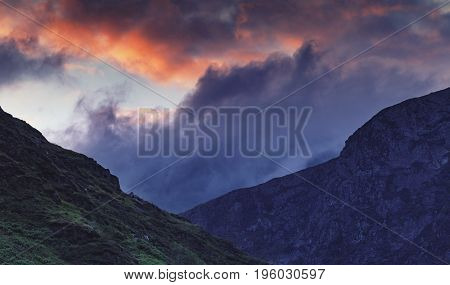 Colorful Dramatic Sunset Clouds over Nant Gwynant Valley Hills in Snowdonia UK