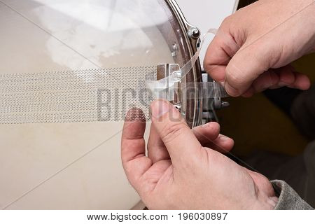 Master hands fixing wire on snare drum overhead view