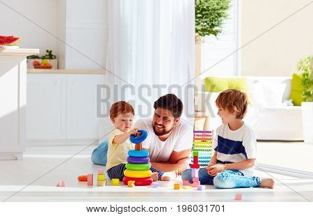 Happy Father Playing With Sons At Home