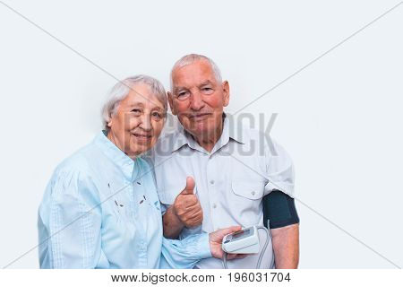 Apparatus measuring the pressure in the hands of an elderly woman and happy old man with sign OK. Tonometer in the wrinkled hands of an elderly person. Concept of good health