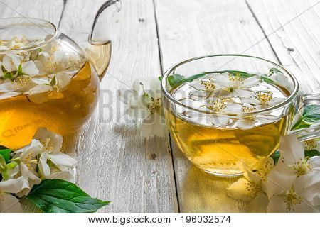 cup of jasmine tea with teapot and Jasmine flowers on rustic wooden background. close up
