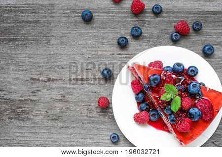 Slice of delicious cheesecake with berry fruits and mint on a plate over rustic wooden table. top view