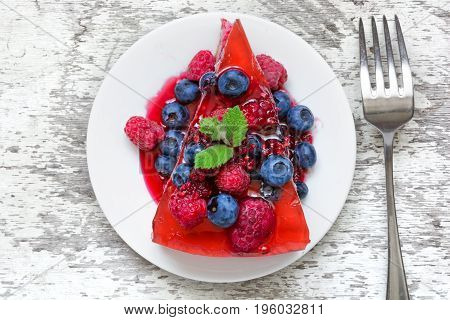 Delicious cheesecake with fresh berries and mint on a plate with fork for healthy breakfast. top view