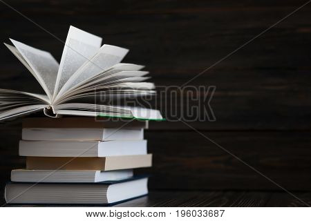 Education concept. Stack of books close up with rustic wooden background. One book is open