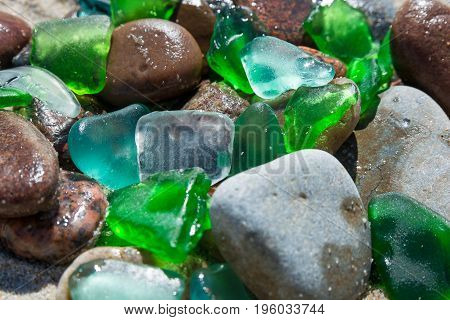 Glass beach. Natural texture with polished sea glass stones and sand. baltic sea. close up