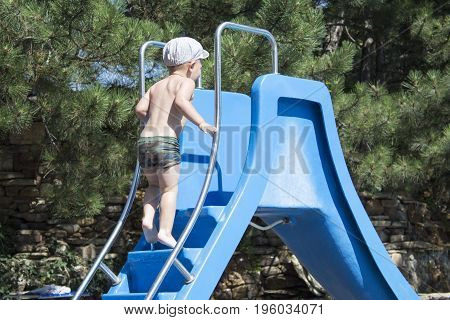 Happy little boy climbing on slide in the pool. children playground near the swimming pool. summer outdoors.