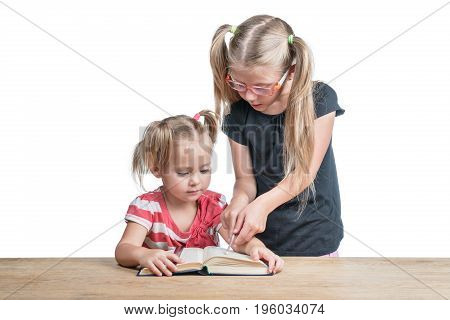Senior sister teaches the younger to read a book lying on a wooden table isolated on a white background