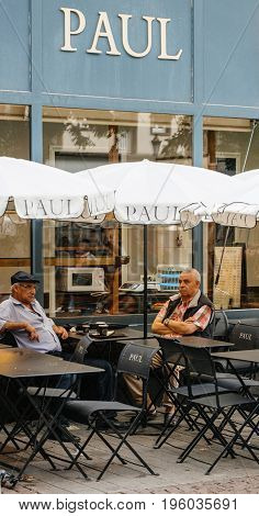 STRASBOURG FRANCE - JUL 12 2017: Paul Boulangerie Et Patisserie cafe with open air terrace on French street and seniors having drinking a cofee. Paul is a French chain of bakery/cafe restaurants established in 1889 in the city of Croix in Northern France