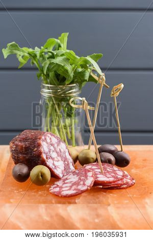 Appetizer of salami green and calamata olives and arugula served on hymalayan pink salt block vertical