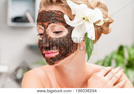 Spa Salon. Beautiful Woman With Chocolate Facial Mask At Beauty Salon