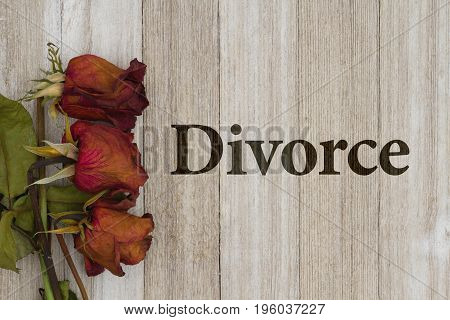 Getting a divorce Dead red roses on weathered wood background with text divorce
