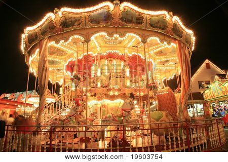 Blurry / long exposure image of a brightly lit Carousel horse ride