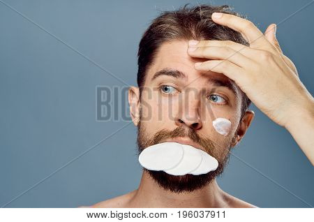 Young guy with a beard on a gray background in the foam, cotton pads, cosmetic cream.