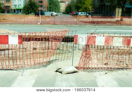 Road barrier in front of the pit hole of road construction site.