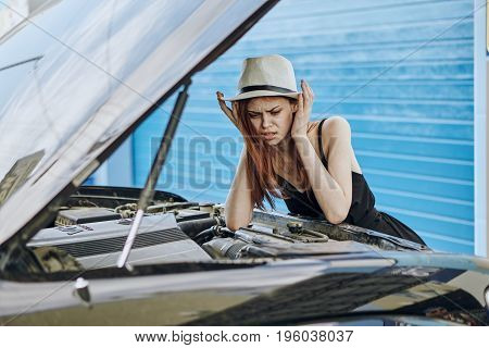 young beautiful woman is trying to repair their car on the street.