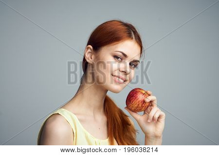 Young beautiful woman on a gray background holds an apple.