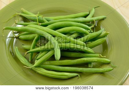 Close up of raw green beans on green plate ready for snapping and stringing
