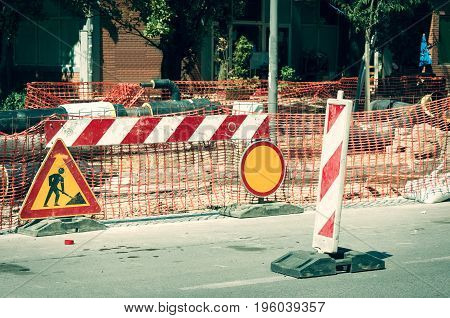 City street construction site with barricades, safety fence net and road work signs.