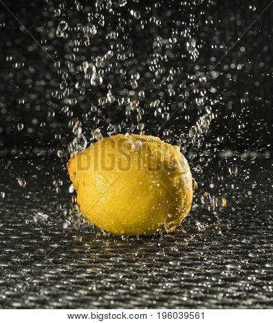 a fresh yellow lemon in the rain