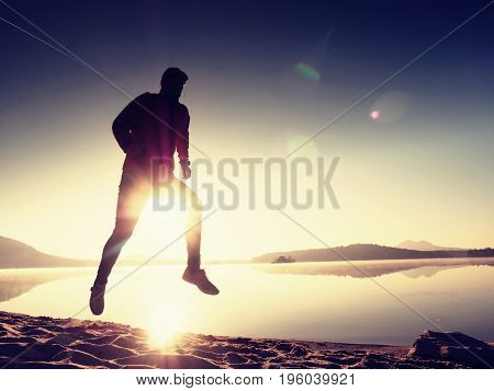 Man Running On Beach Against Backdrop Of A Beautiful Sunset. Sand Of Mountain Lake