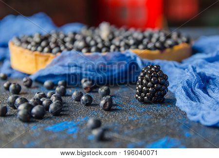 Summer ripe bilberries and blueberries on a blue background. Close up
