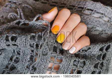 Yellow nail design. Beautiful female hand with manicure with different shades of yellow.