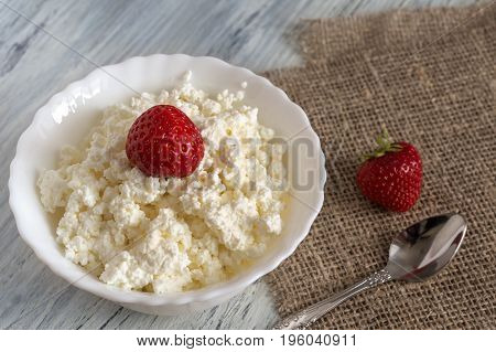 Grainy curd with strawberries on the table with canvas tablecloth