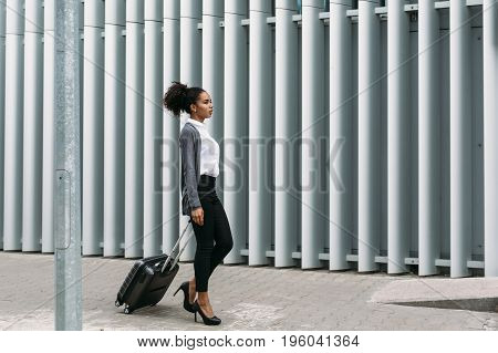Businesswoman with rolling suitcase walking on street, side view