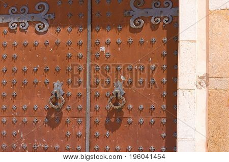 Antique wrought iron door of a church of Sant Bartomeu and Santa Tecla in Sitges Barcelona Catalunya Spain. Close-up