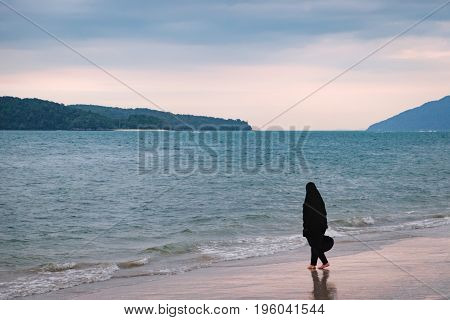 Alone Muslim woman in black hijab resting on the Pantai Tengah Beach, Langkawi Island, Malaysia. Seascape with islands on the horizon.