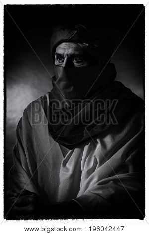 Vintage Black And White Photo Of Berber Man In Night Light Wearing Turban With Robe. Leaning On Cane
