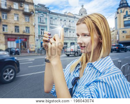 Girl in striped shirt with sunglasses, uses flashlight, on cloudy day,outdoor.Teenager takes pictures on smartphone, holding with both hands, on the background of houses.Looks attentively at screen