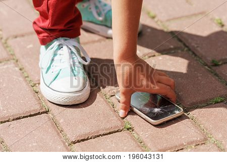 Child Picks Up The Phone With A Broken Screen From The Sidewalk