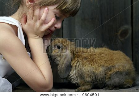 A young girl playing with her bunny