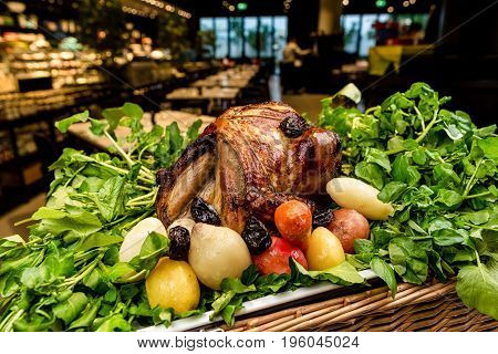 Garnished roasted turkey on platter on picnic basket served with herbs
