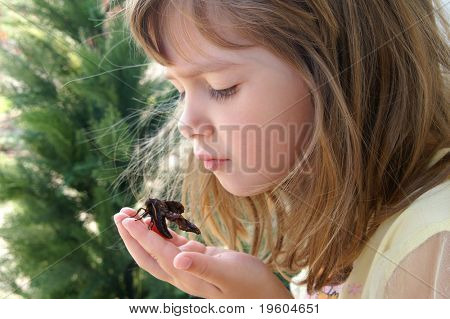 A beautiful young girl holding a moth