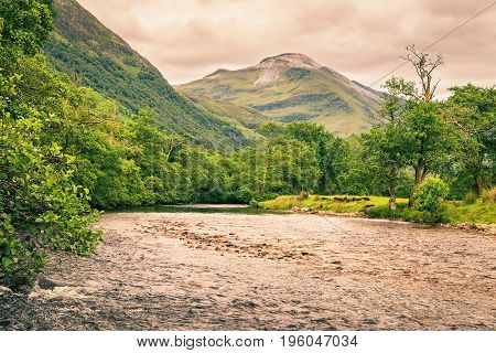 River in Glen Nevis valley Scotland United Kingdom. Cloudy summer evening.