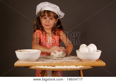A cute young girl kneading her dough to make cookies, wearing a chefs hat and apron