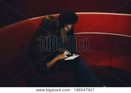 Two businesswomen (caucasian and black with curly afro hair) having discussion about something using digital tablet while sitting in office lounge zone on red curved sofa with white stripes